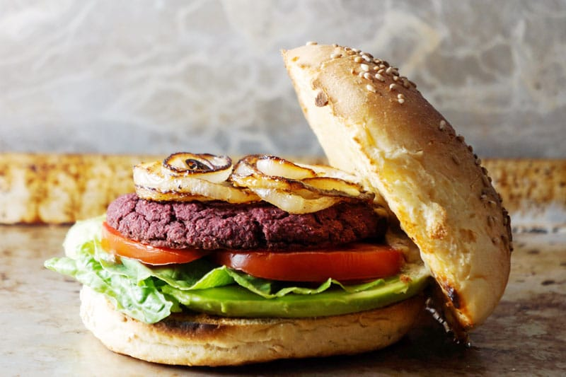 Burger with beet patty, roasted onions, tomato and lettuce