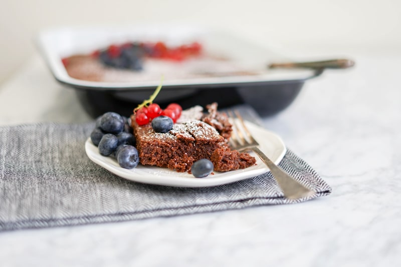 horizontal picture of a close-up brownie on a plate with fresh blueberries