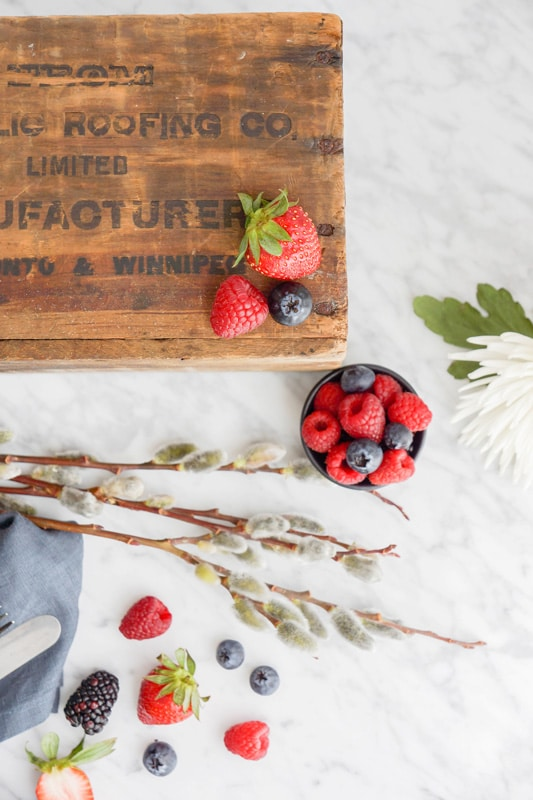 fresh berries in a small black bowl and a wooden box on top of a marble counter with flowers