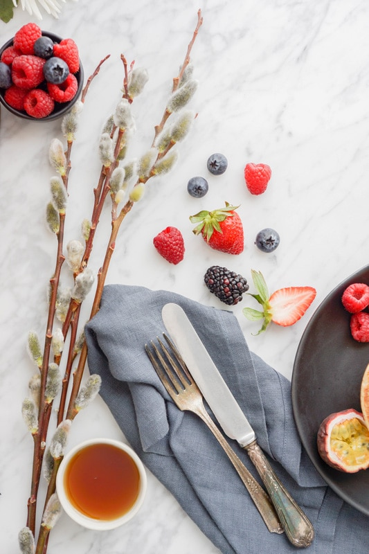 fresh berries with a blue napkin, antique knife and fork on top of a marble background with flowers