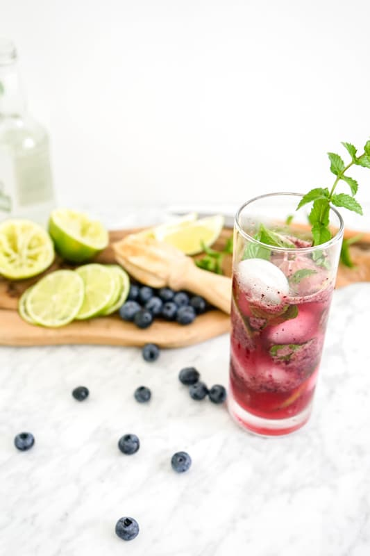 close-up view of a tall glass with a blueberry drink in it and fresh mint sprig with fresh blueberries and limes on a white marble table