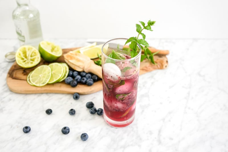 45 degree angle view of a blueberry mojito with blueberries, limes and mint around