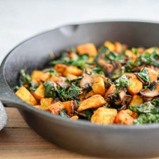 45 degree angle view of Potato, Mushroom and Kale Hash in a cast-iron skillet