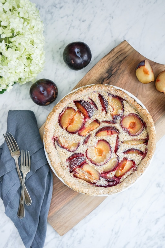aerial view of a French plum tart with fresh plums on the side and a big white hydrangea bloom