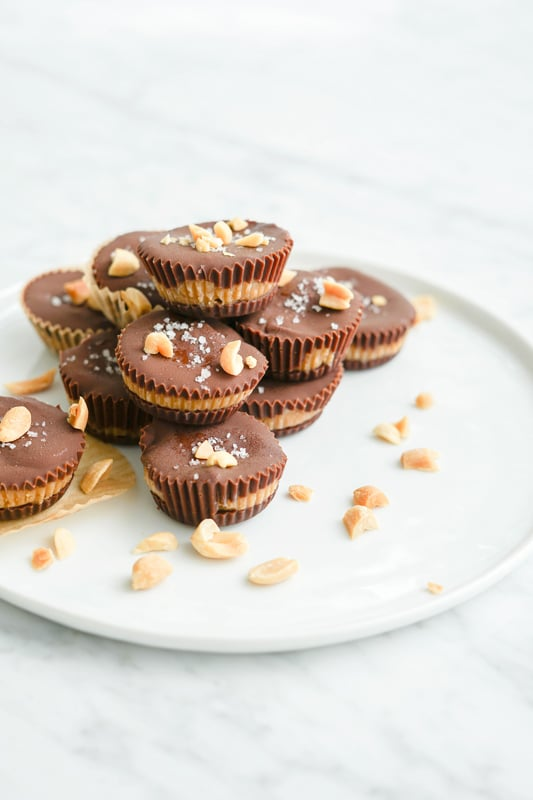Close-up eye-level view of several homemade peanut butter cups on a white plate with peanuts around
