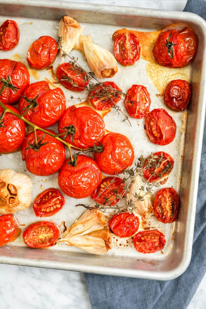 cooked tomatoes on vine and garlic in a sheet pan
