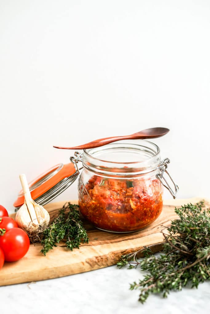 Tomato and garlic confit in a glass canning jar with fresh tomatoes and herbs around it