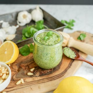 horizontal view of pesto with ingredients scattered on a wood cutting board on a marble table