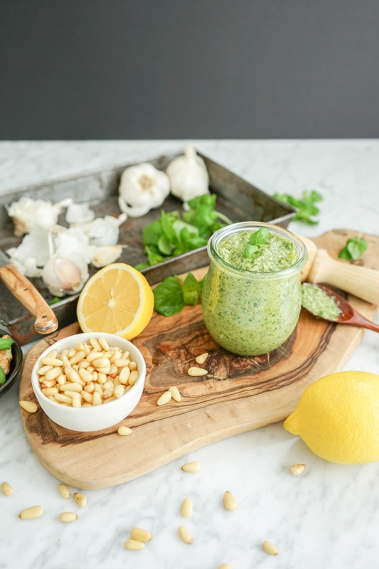vertical view of marble table with pesto ingredients scattered and a small jar of fresh pesto