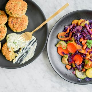 top-down view of chickpea fritters and warm vegetable salad in 2 black plates on a marble table
