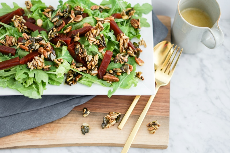 close-up view of a green salad with chopped beets and candied nuts and seeds with golden utensils on the right