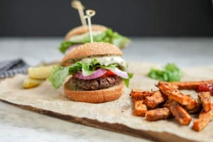 front close-up of a Black Bean Burger with Sweet Potato Wedges on the side