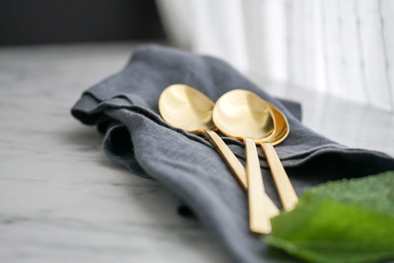 close-up of 3 golden spoons on a blue linen napkin