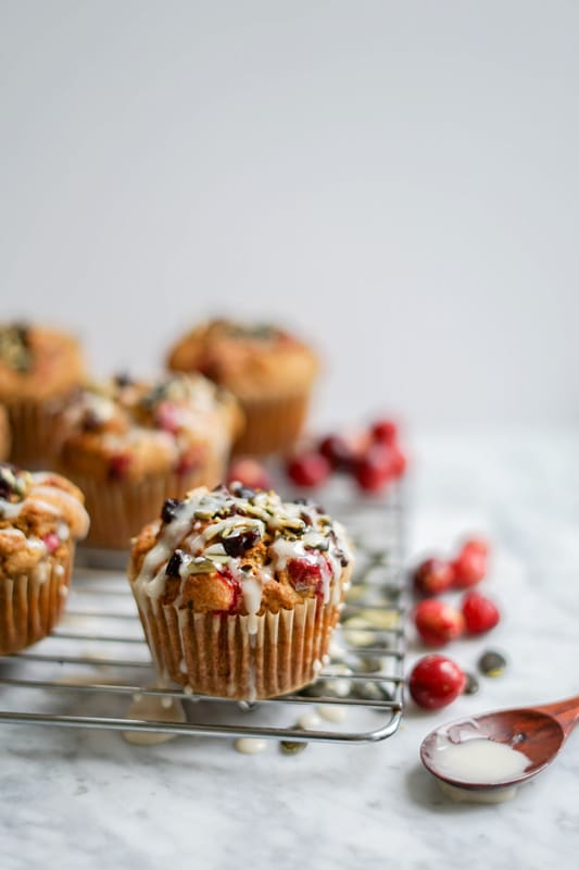 close-up of pumpkin cranberry muffins with icing dripping on top