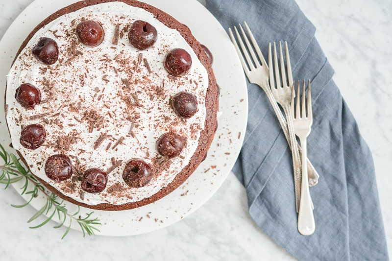 top down view of a chocolate cake with whipped coconut cream and cherries on top