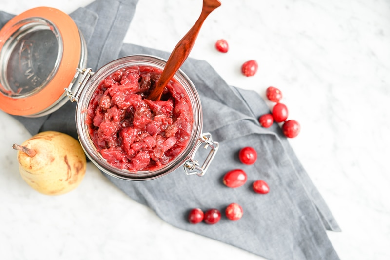top-down view of cranberry chutney in glass jar on top of a grey linen napkin and fresh cranberries scattered around