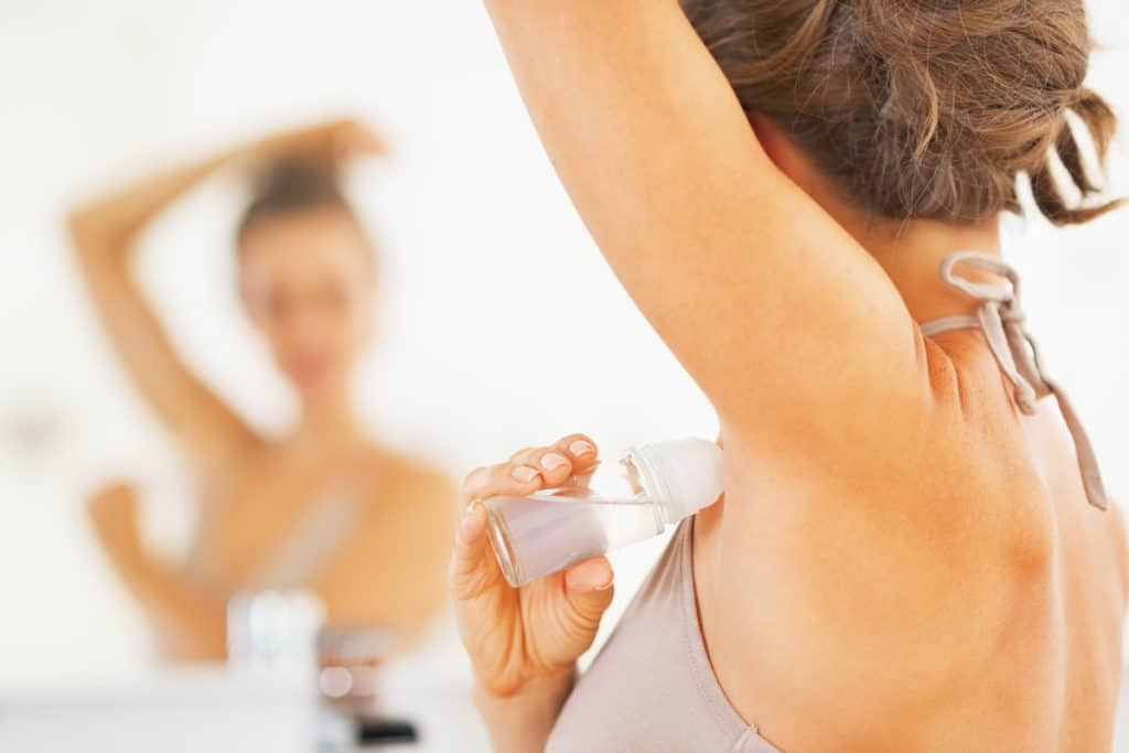 Woman applying stick of deodorant to armpit