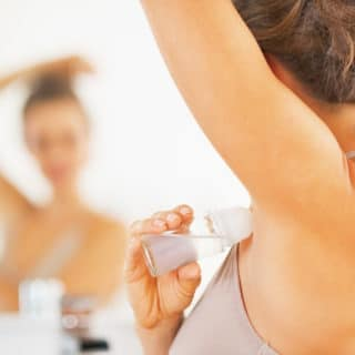Woman applying stick of deodorant to armpit