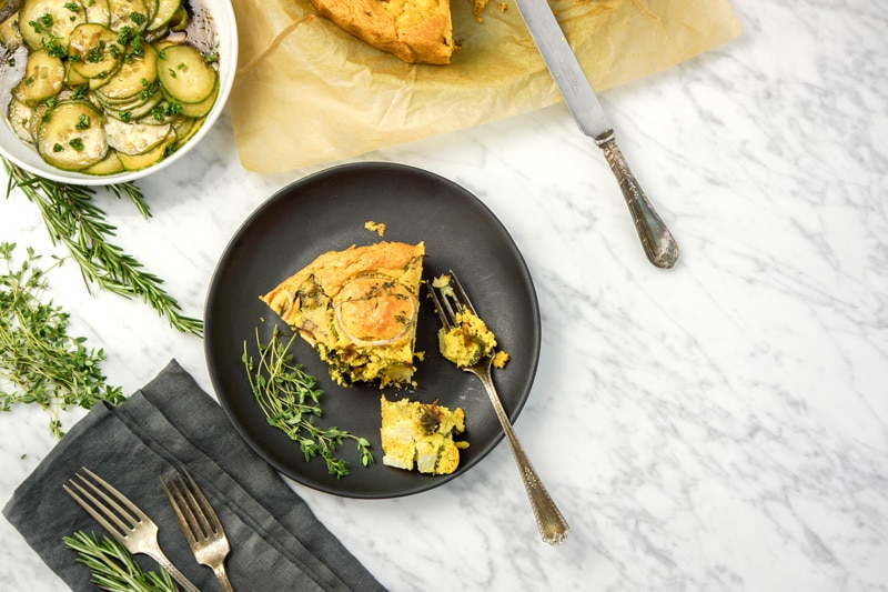 horizontal aerial view of a piece of the cauliflower cake on a black plate with an antique fork, on a white marble table. antique forks on a grey napkin, fresh herbs and a small white dish with a cucumber salad on the left side, a partial view of the cake in the back