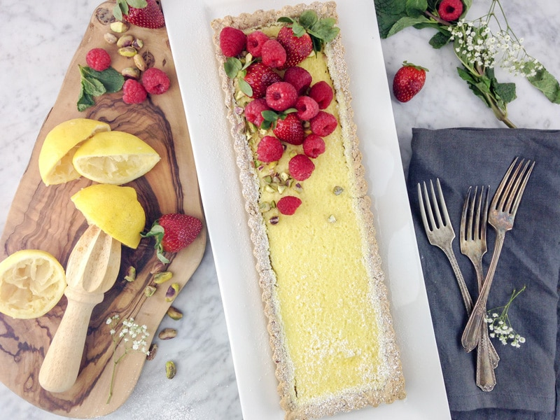 horizontal aerial view of a rectangular lemon tart on a white plate, with raspberries and strawberries on top, and some squeezed lemon halves and fresh berries on a wood board on the left side and forks on a grey napkin on the right side