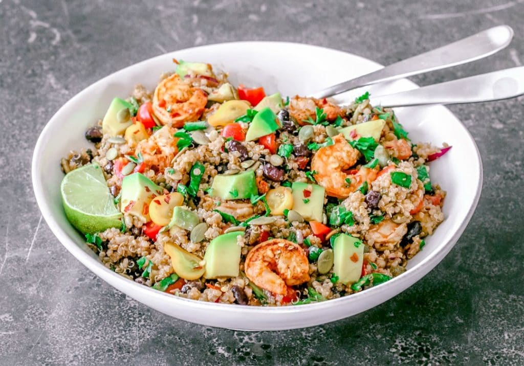 Front view close-up of a white bowl with quinoa, avocado cubes and shrimp salad