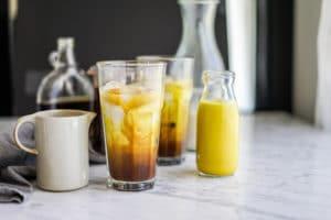 a small glass bottle of yellow golden milk with a tall glass of golden milk swirl with coffee and cashew milk