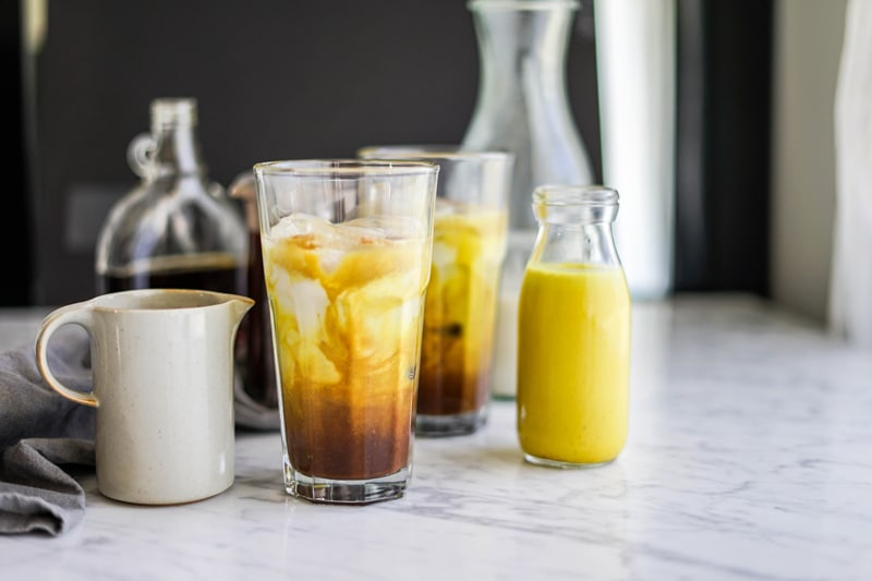 a small glass bottle of yellow golden milk with a tall glass of iced golden milk mocha latte swirling