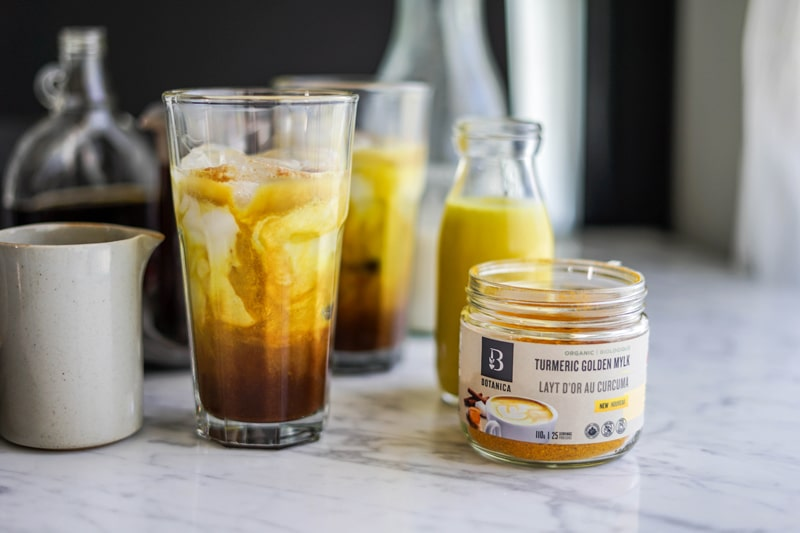 A tall glass of golden milk and coffee with a jar of Botanica Golden Mylk