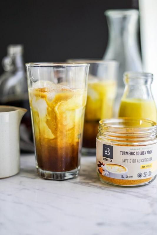 a glass of iced golden milk mocha latte beside a jar of Botanica's organic golden mylk